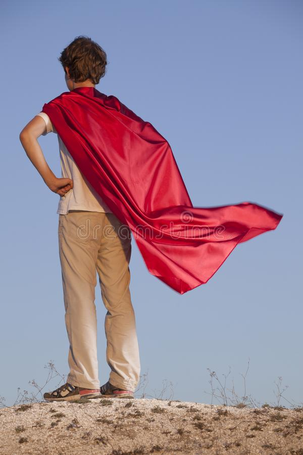 Boy playing superheroes on the sky background, teenage superhero in a red cloak on hill royalty free stock photos