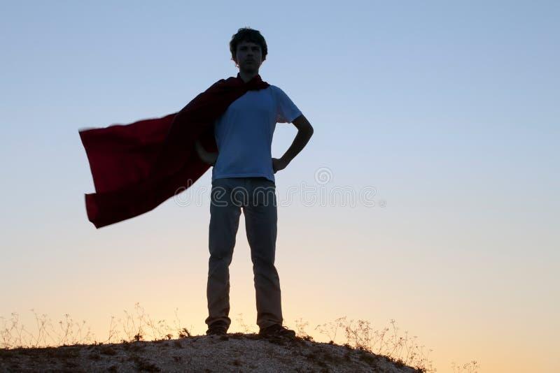 Boy playing superheroes on the sky background, teenage superhero stock images