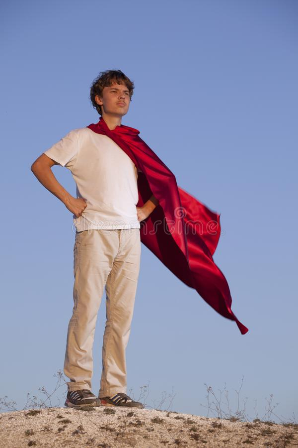 Boy playing superheroes on the sky background, teenage superhero in a red cloak on hill royalty free stock image