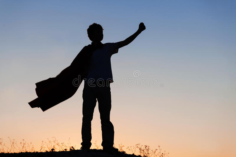 Boy playing superheroes on the sky background, teenage superhero royalty free stock images