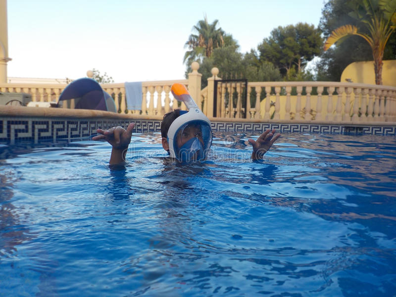 A boy is playing in a swimming pool with Easybreath mask royalty free stock photography