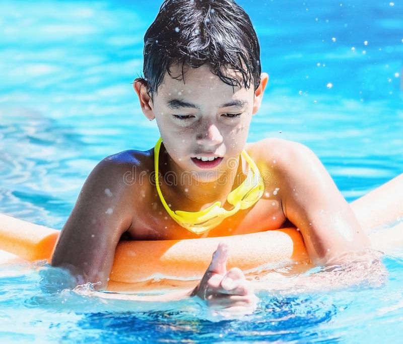 Boy playing on the swimming pool pressing the water with hands a royalty free stock photo