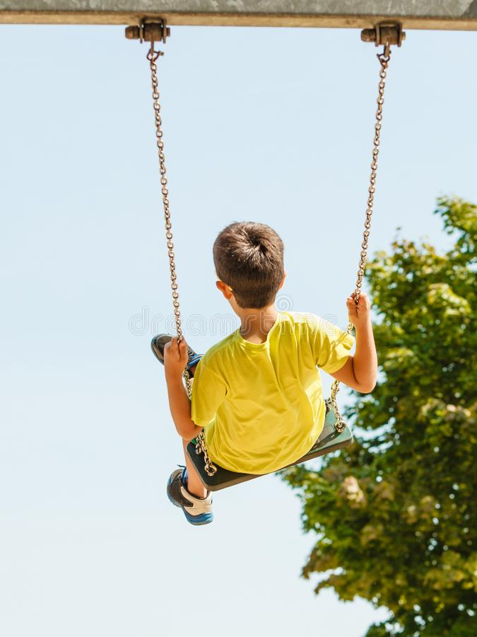 Boy playing swinging by swing-set. stock images