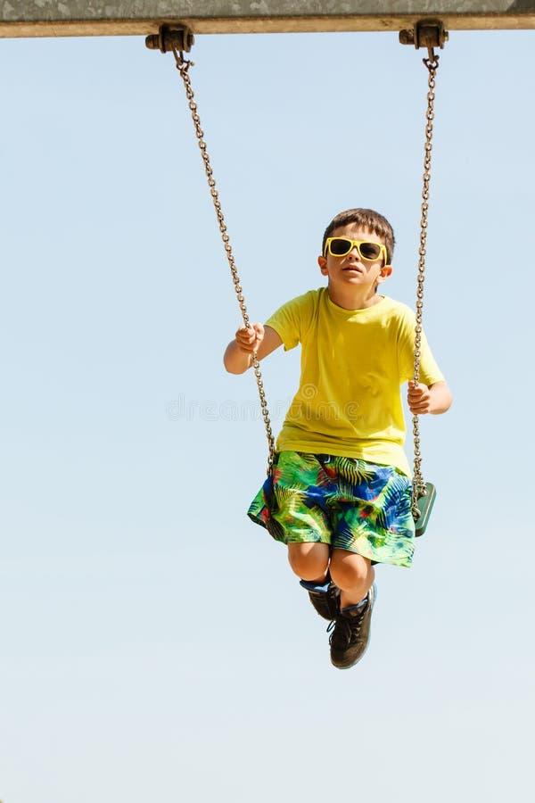 Boy playing swinging by swing-set. stock image