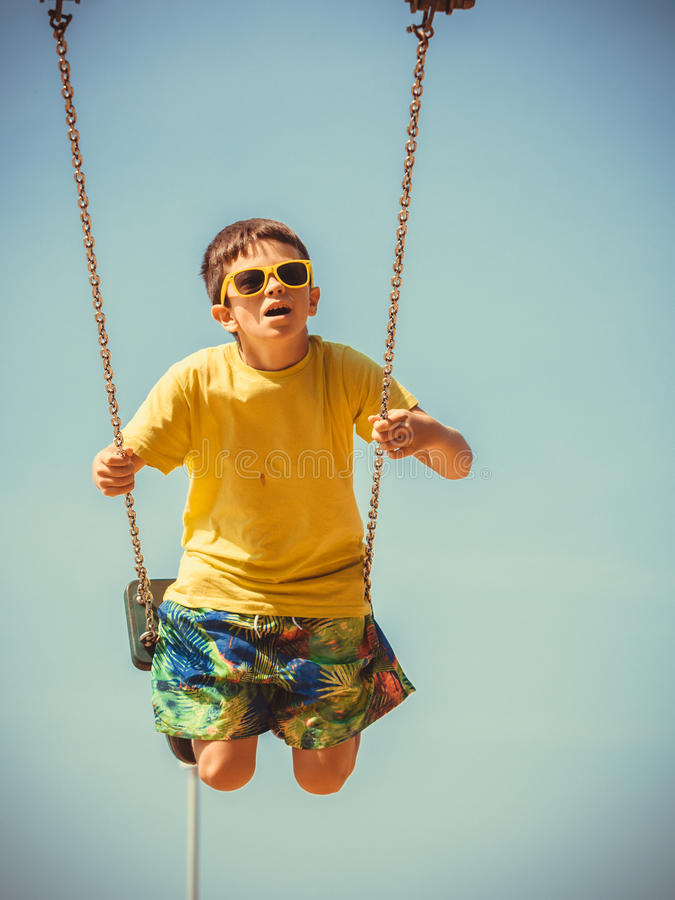 Boy playing swinging by swing-set. stock photo