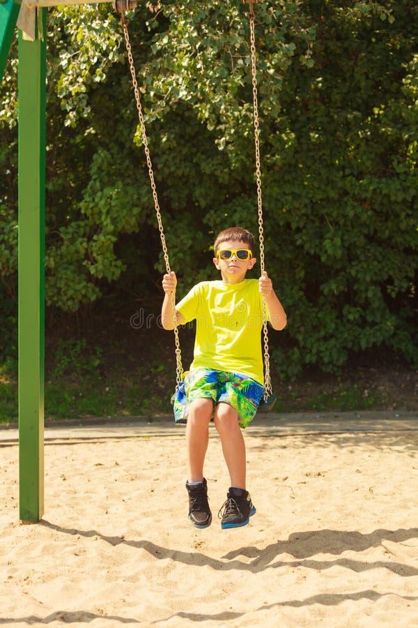 Boy playing swinging by swing-set. royalty free stock image