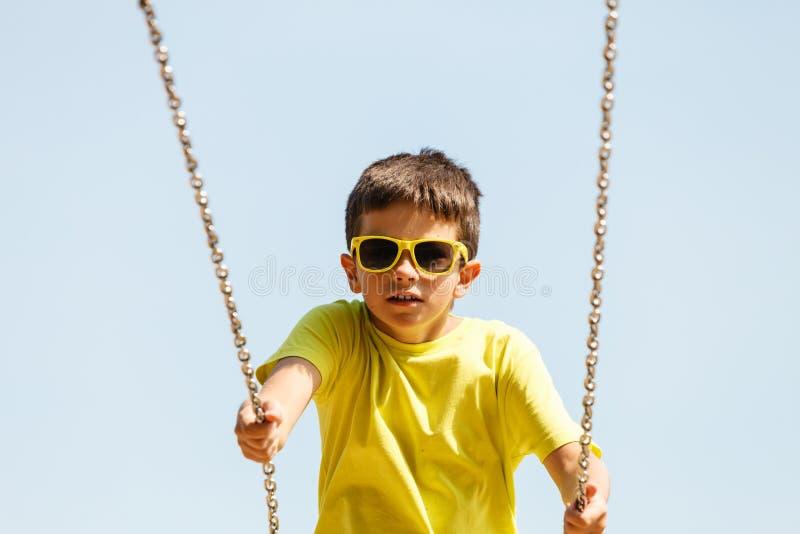 Boy playing swinging by swing-set. royalty free stock photos