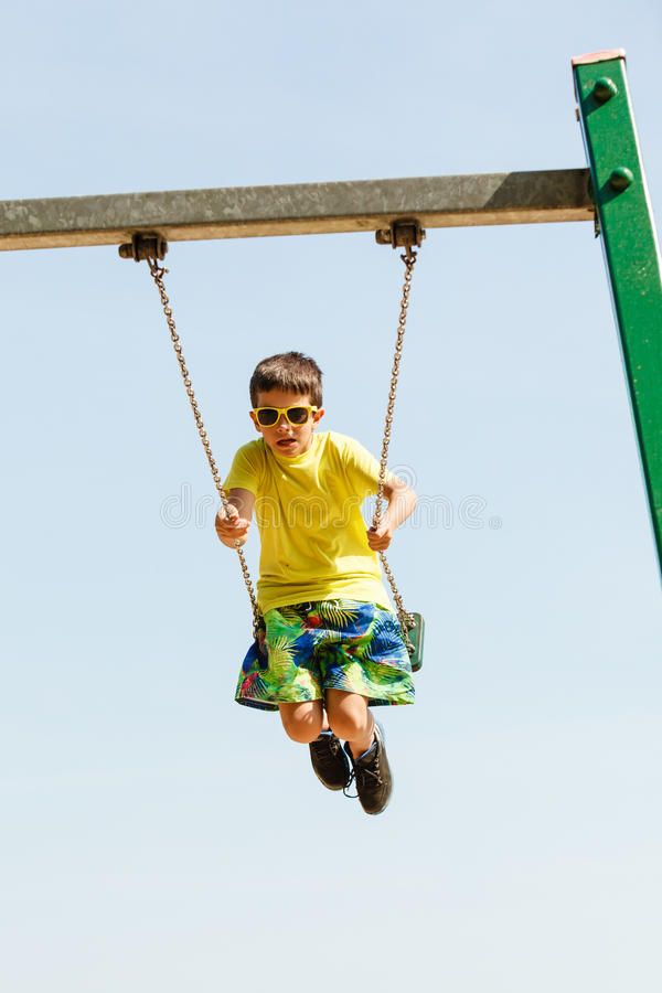 Boy playing swinging by swing-set. royalty free stock images