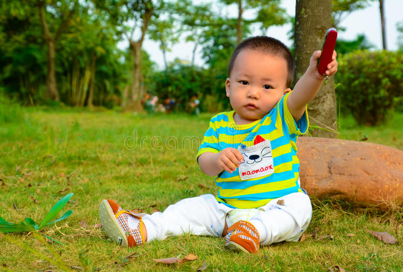 The boy playing in the Swiss Army knife on the lawn stock photos