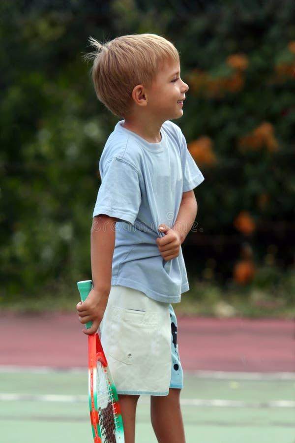 Boy playing tennis stock photos