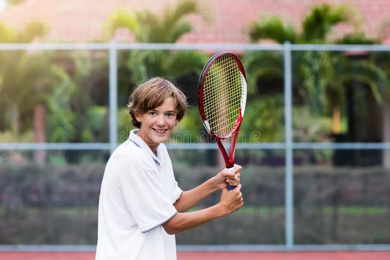 Child playing tennis on outdoor court royalty free stock photography