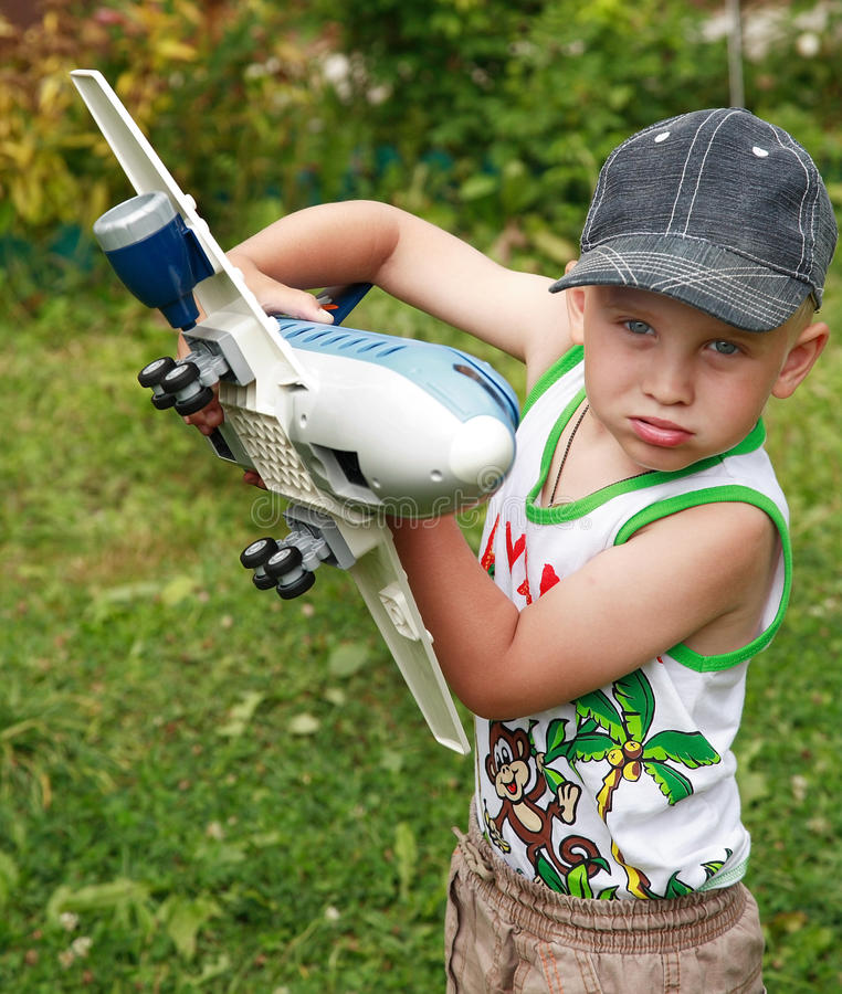 The boy playing with toy airplane royalty free stock photo