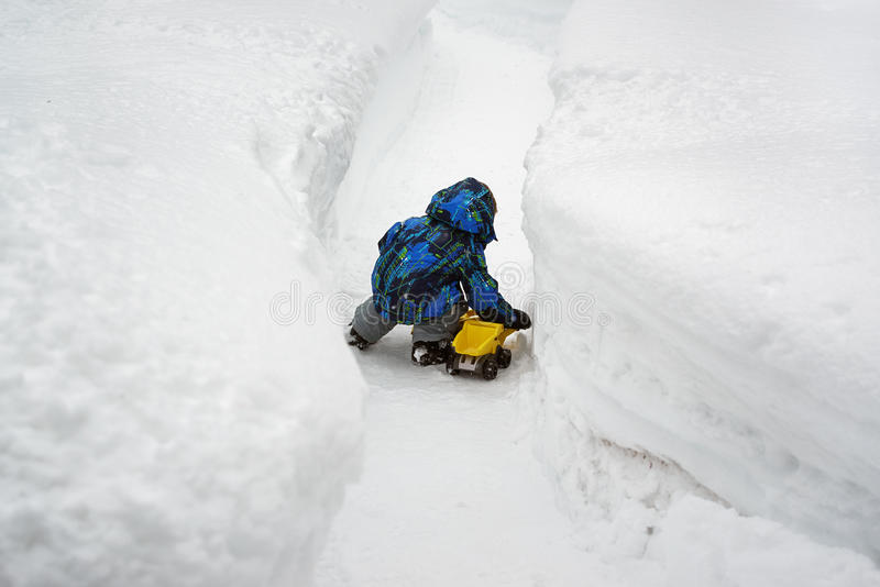 Boy Playing with Toy Truck in Deep Snow. A little boy dressed in a snowsuit is crouched down outside playing with a yellow toy dump truck in a cleared snow path stock photos