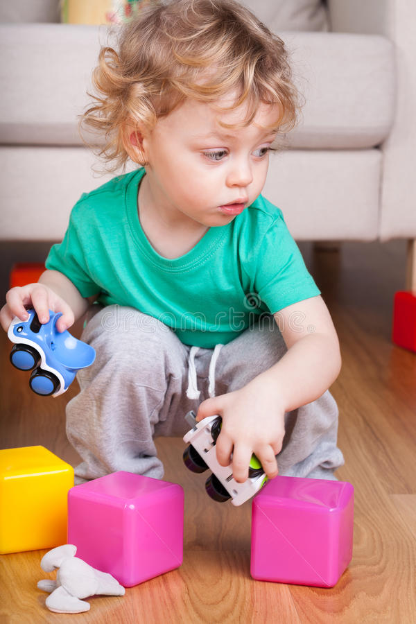 Boy playing with toys on the floor. Little boy playing with toys on the floor stock photo