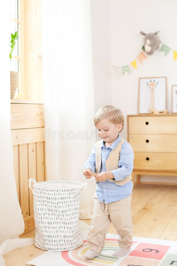 Boy playing with toys in the room. Eco-friendly children`s room decor in the Scandinavian style. Portrait of a boy playing in kind stock photos