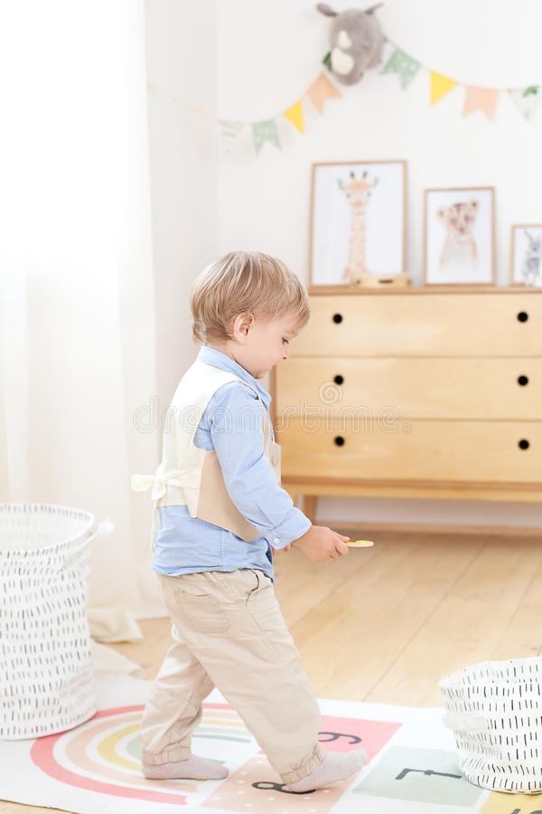 Boy playing with toys in the room. Eco-friendly children`s room decor in the Scandinavian style. Portrait of a boy playing in kind royalty free stock photos