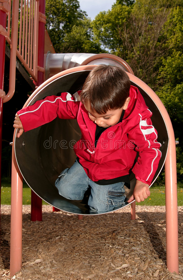 Boy playing in a tube slide stock image