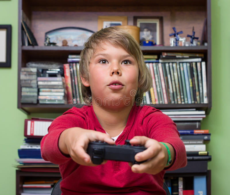 Boy playing a video game console. stock photography