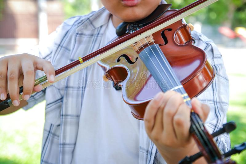 Asian boy playing violin music stock photos