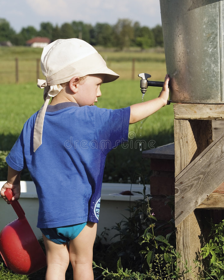 Download Boy Playing At Water Barrel Royalty Free Stock Images - Image: 5263599