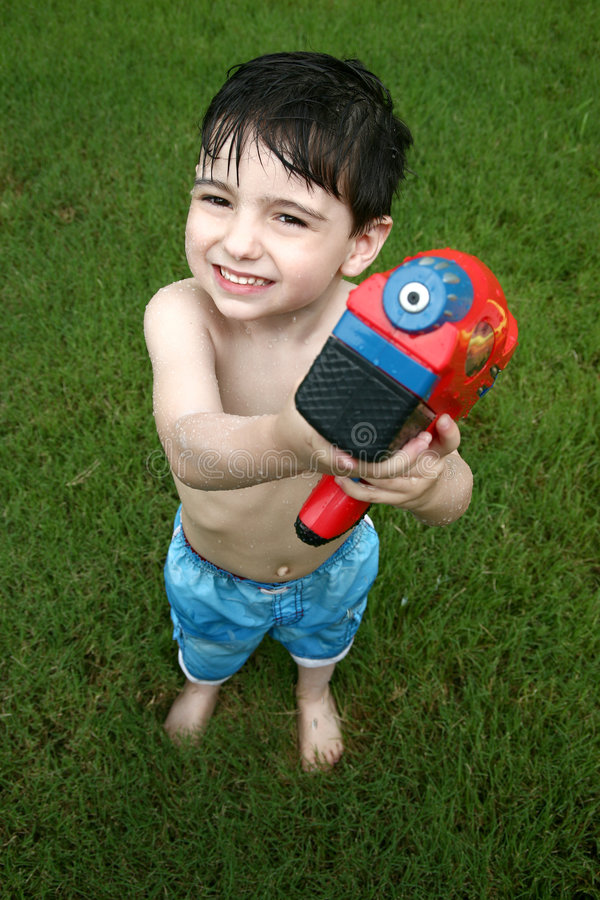 Boy Playing with Water Gun. Adorable four year old boy playing with water gun outside in grass stock image