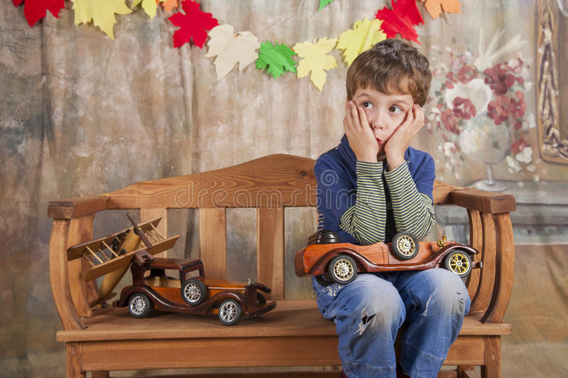 Boy playing with wooden toy cars. stock image