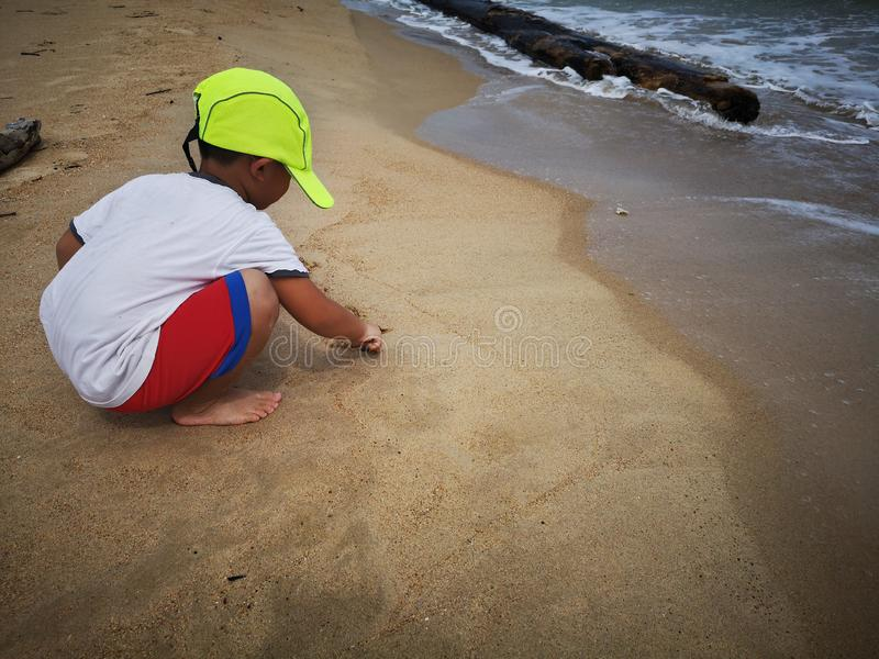 A boy playing and written words on the sandy beach. royalty free stock photo