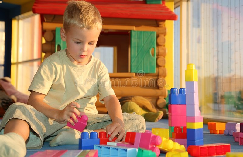 Boy in playroom. Playing with toy blocks stock photography