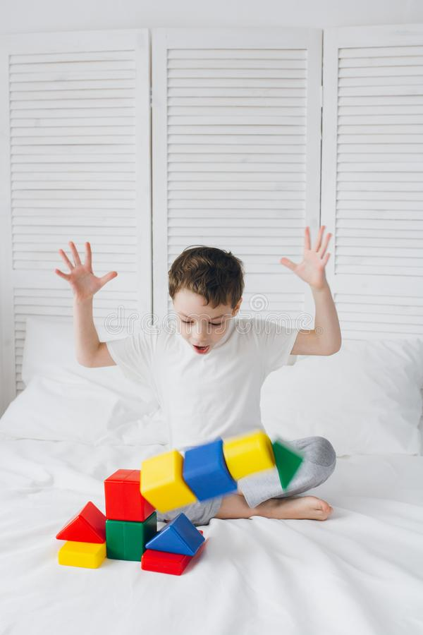 Boy plays and builds a tower of colorful plastic cubes stock photography