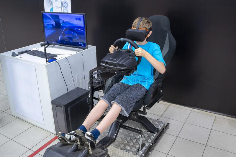 A boy plays on the car simulator stock image
