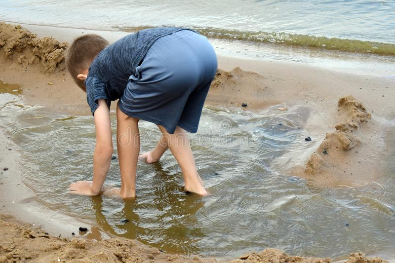 Boy plays dirt on the river bank in  summer. Active children`s holiday outdoor royalty free stock image