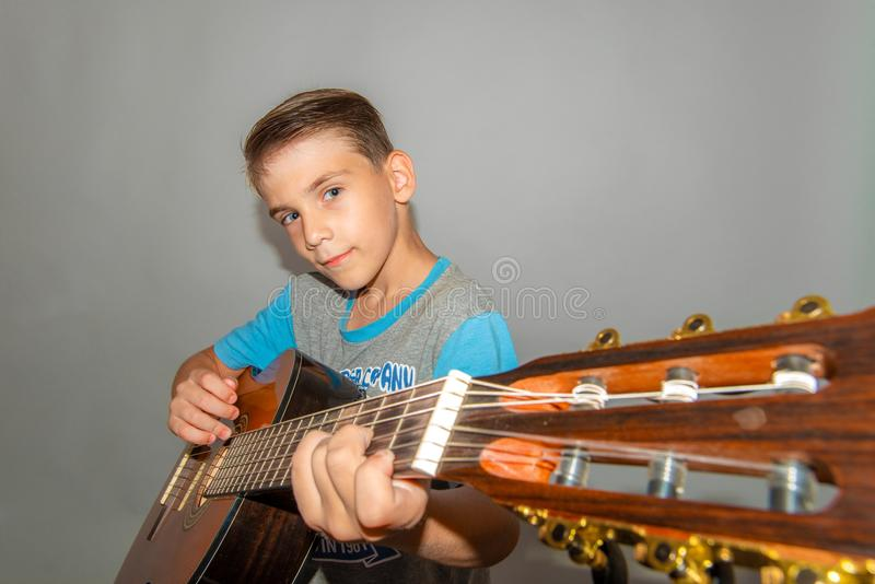 A boy plays the guitar on a gray background in the studio, wide-angle close-up photo royalty free stock photo
