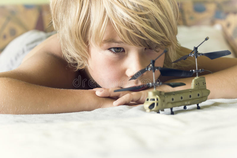 Boy plays with a helicopter. On the bed stock photography