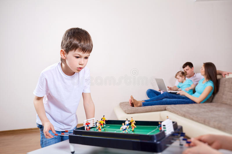 Boy plays at home in board games. Parents relax stock photography