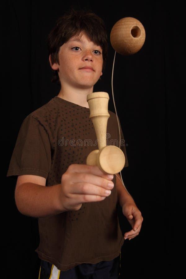Boy plays with Kendama toy stock photos