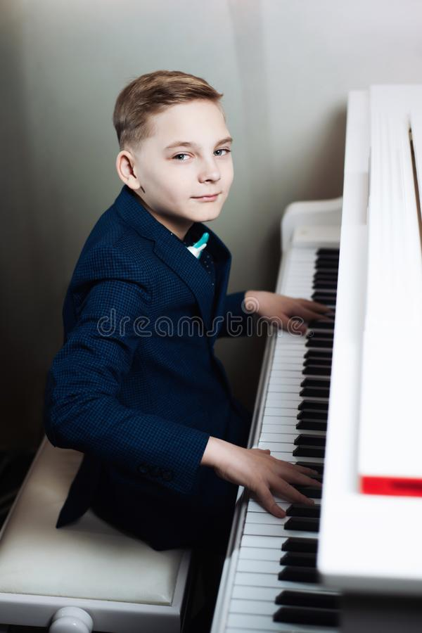 Boy plays the piano. Stylish child learns to play a musical instrument royalty free stock photo