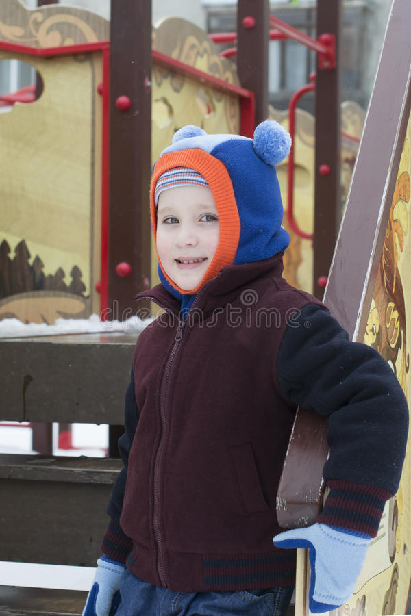 The boy plays on the playground in the winter stock photo