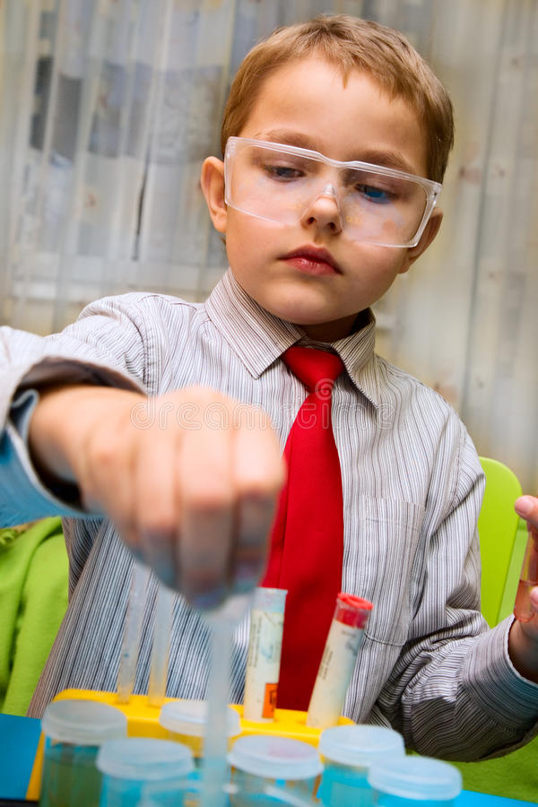 A boy plays in the scientist chemist royalty free stock photography