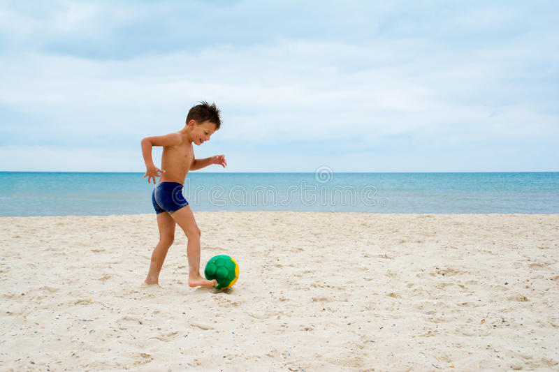 Boy plays soccer on beach stock images