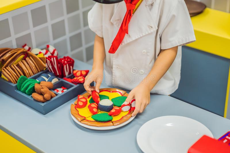 The boy plays in the toy kitchen, cooks a pizza stock photo