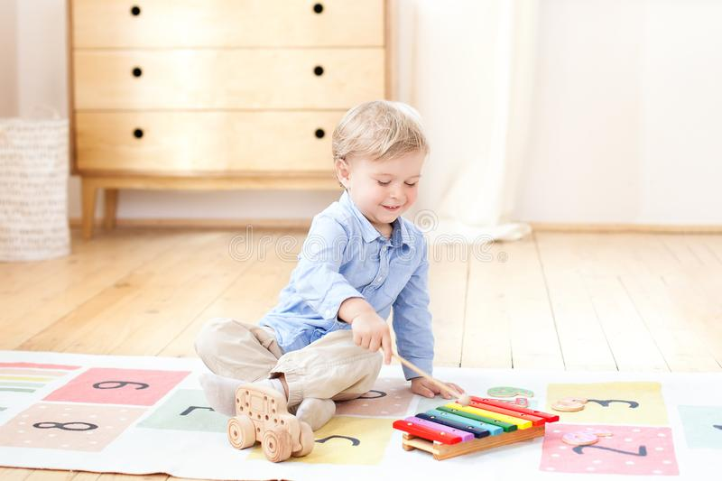 The boy plays xylophone at home. Cute smiling positive boy playing with a toy musical instrument xylophone in the children`s white royalty free stock photos