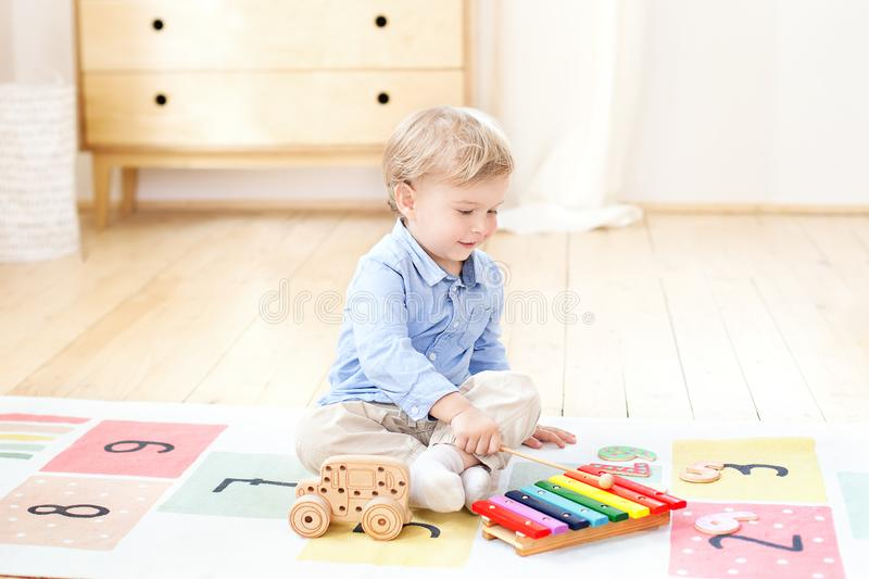 The boy plays xylophone at home. Cute smiling positive boy playing with a toy musical instrument xylophone in the children`s white royalty free stock photography