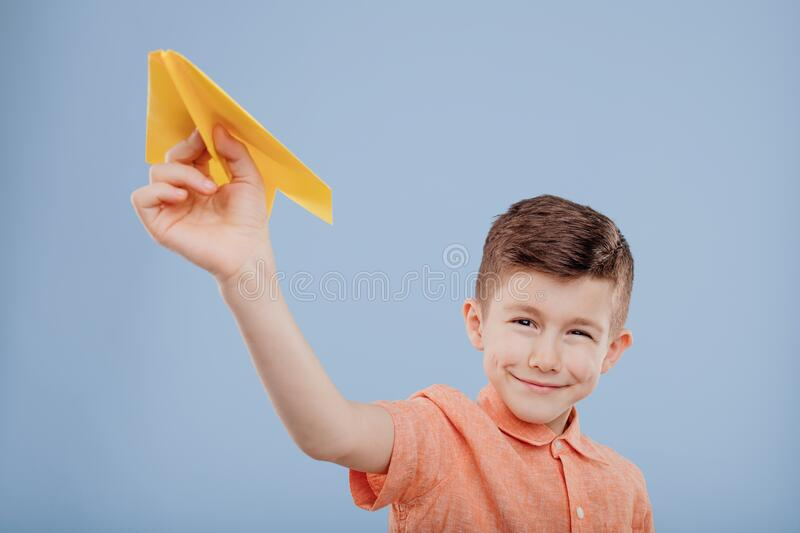 Boy plays with yellow paper plane, looks at the camera, stock images