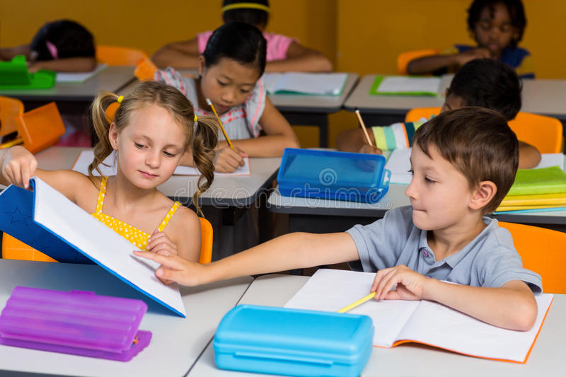 Boy pointing at book showed by classmate. Cute boy pointing at book showed by classmate in classroom stock photos