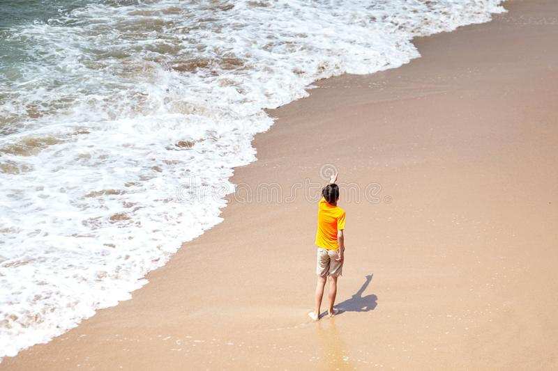 Boy pointing his hand away, kid playing on a sandy beach by the sea water royalty free stock images