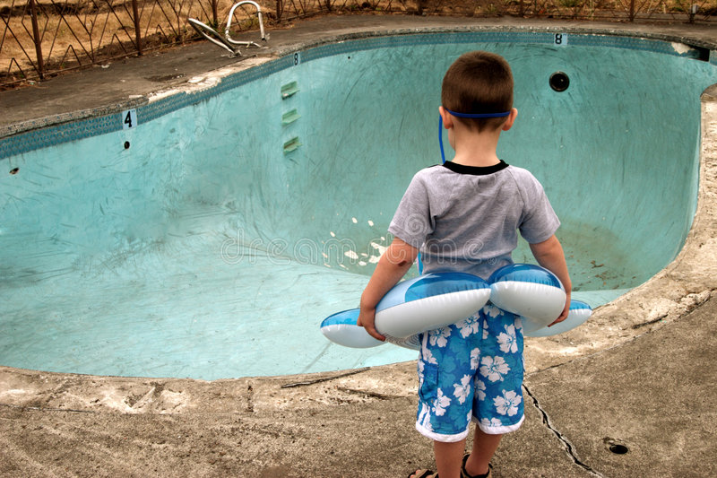 Boy at Pool. A young boy ready for a swim finds an empty pool waiting for him