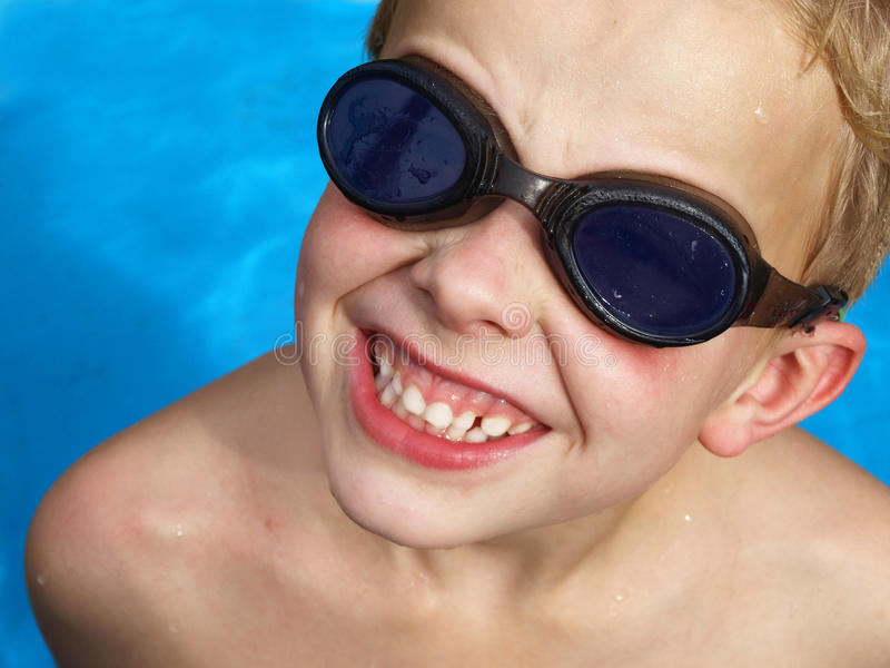 Boy in pool. Boy in a pool wearing goggles royalty free stock photo