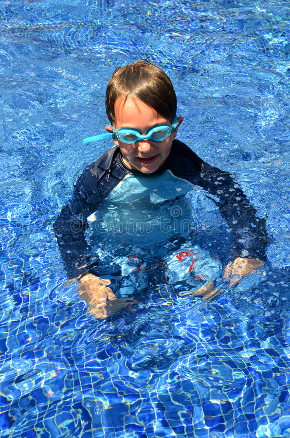 Boy in a pool wearing goggles royalty free stock photography