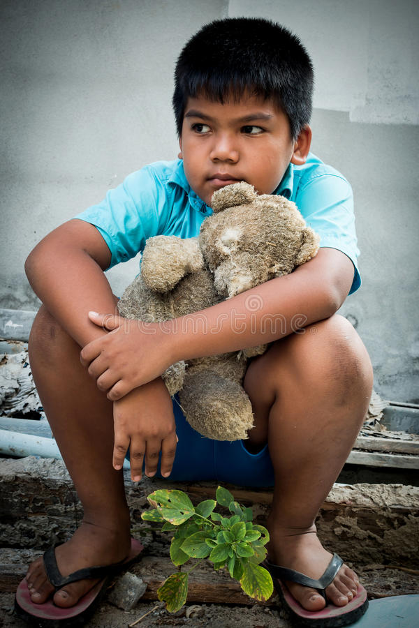 Boy poor with old teddy bear. Sitting on old wood pile royalty free stock image
