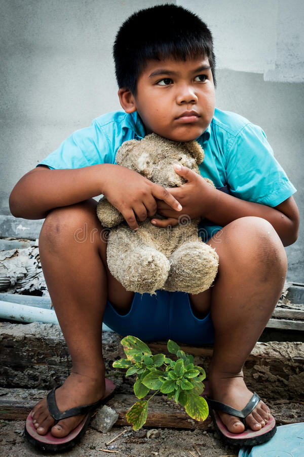 Boy poor with old teddy bear. Sitting on old wood pile royalty free stock images